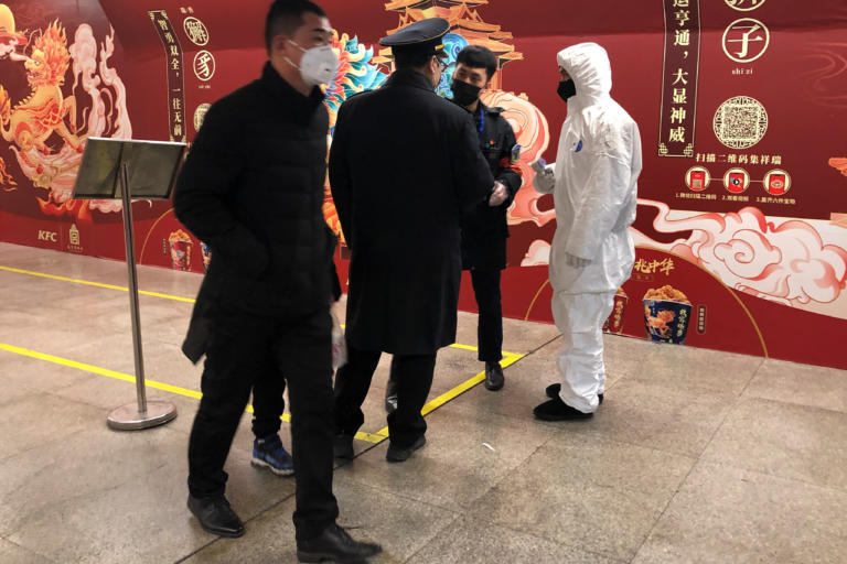 A worker in a protective suit speaks with staff members at the Wangfujing subway station, as the country is hit by an outbreak of the new coronavirus, in Beijing