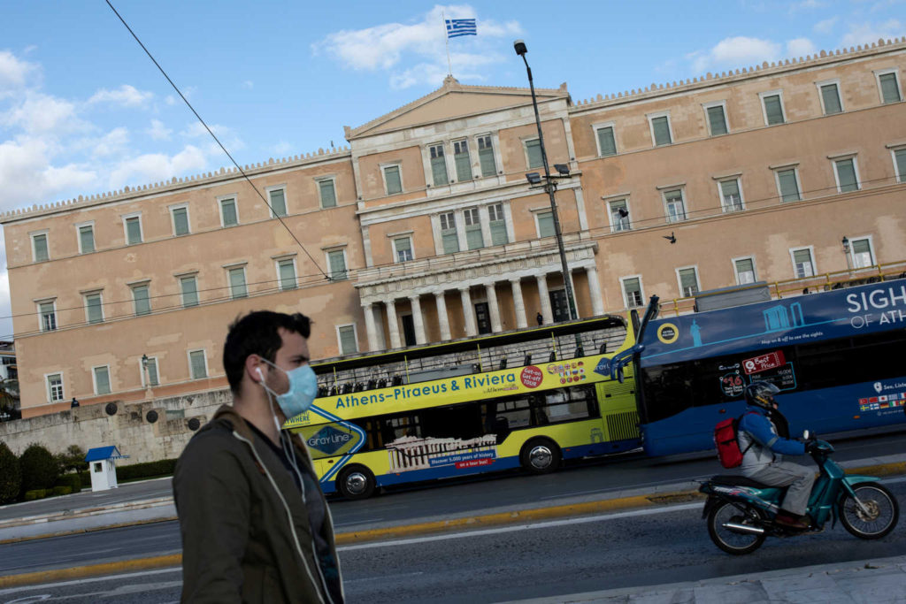 FILE PHOTO: A man wearing a protective face mask walks past the parliament building, as the Greek government implemented strict precautionary measures against spread of the coronavirus disease (COVID-19), in Athens