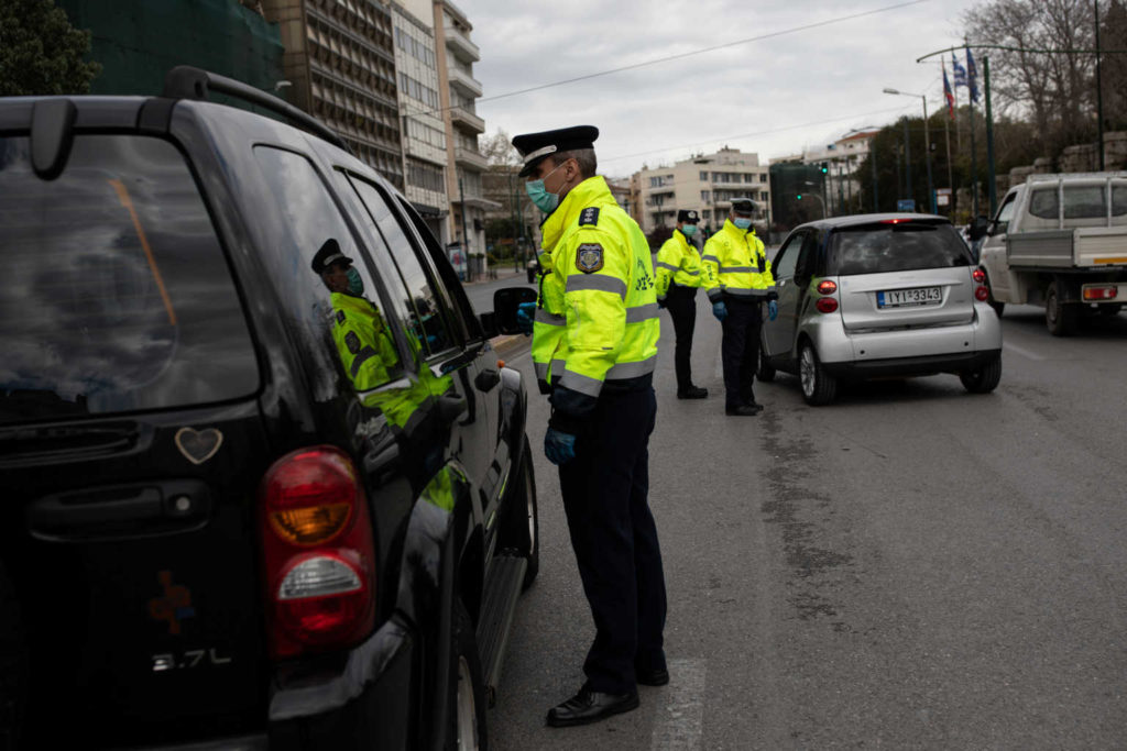 Police officers perform checks on drivers documents verifying purpose of movement, after the Greek government imposed a nationwide lockdown to contain the spread of the coronavirus disease (COVID-19), in Athens