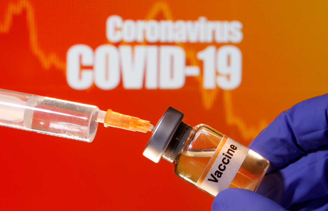 """A small bottle labeled with a """"Vaccine"""" sticker is held near a medical syringe in front of displayed """"Coronavirus COVID-19"""" words in this illustration"""